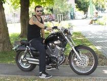 Rebellischer junger Mann auf einem Motorrad lizenzfreie stockfotos