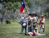 Rebels In Combat. Red Bluff, California, United States-April 25, 2015: Confederate infantry advance towards the Union lines during a Civil War reenactment Royalty Free Stock Photo