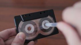 Rebobine manualmente una cinta de casete con una pluma almacen de metraje de vídeo