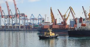 Rebocador na curva do navio de carga, ajudando à embarcação a manobrar no porto marítimo fotografia de stock royalty free