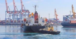Rebocador na curva do navio de carga, ajudando à embarcação a manobrar no porto marítimo imagem de stock royalty free