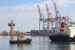 Rebocador que ajuda ao navio de carga manobrado no porto de Odessa, Ucrânia foto de stock royalty free