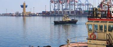 Rebocador que ajuda ao navio de carga manobrado no porto de Odessa, Ucrânia foto de stock