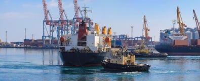 Rebocador que ajuda ao navio de carga manobrado no porto de Odessa, Ucrânia fotos de stock royalty free