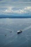 Rebocadores que vêm ajudar a um navio de recipiente Imagens de Stock Royalty Free
