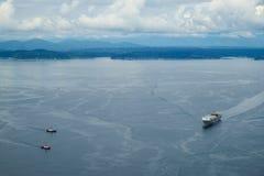 Rebocadores que vêm ajudar a um navio de recipiente Fotografia de Stock Royalty Free