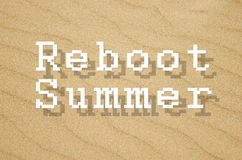 Reboot summer written on yellow sand background Royalty Free Stock Photo