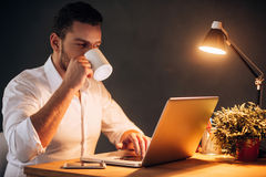 Rebooting his energy to work more. Confident young man drinking coffee while sitting at his working place at night time Royalty Free Stock Photo