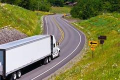 Reboque branco do caminhão na estrada de enrolamento entre montes verdes Imagem de Stock Royalty Free
