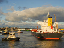 Reboque a embarcação que ajuda ao navio de carga da maioria a deixar o cais Fotografia de Stock