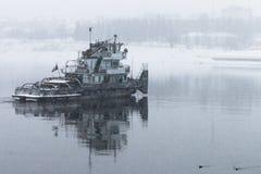 Reboque o barco no rio na neve fotografia de stock