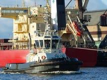 Reboque o porto entrando da embarcação, navio de carga da maioria no fundo Imagem de Stock