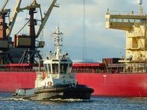 Reboque o porto entrando da embarcação, navio de carga da maioria no fundo Fotos de Stock