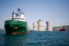 Reboquees que rebocam a plataforma petrolífera a pouca distância do mar da base fotografia de stock