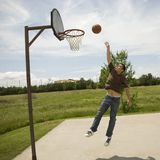 Rebound. Young man jumping up to rebound a goal on a bright sunny day on an outdoor basketball court Stock Photo