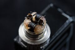Rebuildable dripping atomizer for vaping. Or e-cigarette with coil and cotton stripes wetted with e-liquid, modern vape device for quit smoking, macro photo royalty free stock photo