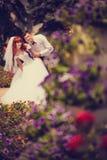 Recém-casados do retrato entre as rosas de florescência Fotos de Stock Royalty Free