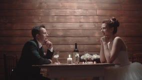 Rec?m-casados em um vestido de casamento, sentando-se em um restaurante e falando, durante o jantar video estoque