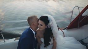Recém-casados felizes que passam o tempo em um veleiro na água aberta junto O noivo sussurra maciamente na orelha da noiva video estoque