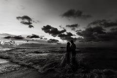 Recém-casados na praia no por do sol imagem de stock