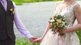 Recém-casados no fundo do rio que guarda as mãos, vestido bonito do ` s da noiva vídeos de arquivo