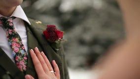 Recém-casados noivo e beijo e curso do abraço da noiva na floresta sempre-verde nevado durante a queda de neve no movimento lento filme