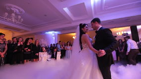 Recém-casados novos bonitos que dançam sua primeira dança encoberta pelas emanações brancas Celebração do casamento no restaurant
