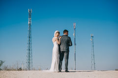 Recém-casados que beijam passionately ao estar na estrada foto de stock