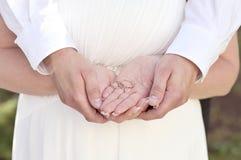 Recém-casados que guardam as alianças de casamento de prata nas mãos fotografia de stock royalty free