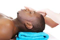 Recaiving Kopfmassage des schwarzen Mannes am Badekurort. Stockfotos