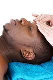 Recaiving Kopfmassage des schwarzen Mannes am Badekurort. Stockbild
