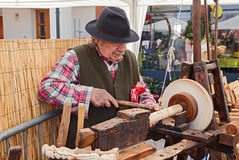 An artisan working the wood with an antique lathe. Recalling of ancient craft: an artisan working the wood with an antique treadle lathe at festival La soffitta Royalty Free Stock Photography