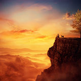 Recalling childhood. Young man with his faithful dog standing on the peak of a cliff watching the sunset over valley. Recalling childhood memories, friendship Stock Photos