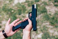 Recargue el arma en su mano Entrenamiento en el tiroteo foto de archivo libre de regalías