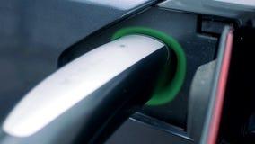 Recarregando o processo de um carro elétrico com seu soquete que está sendo iluminado video estoque