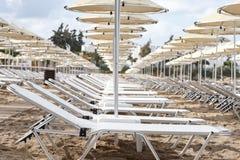 Receding row of beach chairs under umbrellas. Receding row of comfortable reclining beach chairs under umbrellas on a sandy tropical beach on a hot summer day stock photo