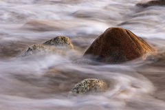 Receding Tide. A rock showing the movement of water with a receding tide royalty free stock images