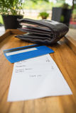 Receipt and credit card with wallet on wooden tray. Royalty Free Stock Photo