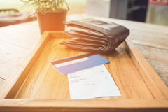 Receipt and credit card with wallet on wooden tray vintage tone. Royalty Free Stock Photos