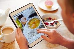 Receita App de Person At Breakfast Looking At na tabuleta de Digitas foto de stock royalty free