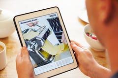 Receita App de Person At Breakfast Looking At na tabuleta de Digitas imagem de stock royalty free