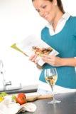 Receita da leitura da mulher que cozinha a salada da cozinha do livro Imagem de Stock Royalty Free