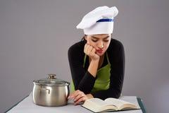 Receita da leitura do cozinheiro chefe da mulher Imagens de Stock