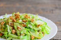 Receita do slaw da couve da pera Salada simples com pera, couve e as nozes cruas em uma placa Fundo de madeira rústico Comer limp imagens de stock royalty free