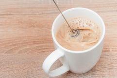 A receita para o café claro aromático delicioso com leite e espuma em um copo branco em uma tabela de madeira na cozinha para um  foto de stock royalty free