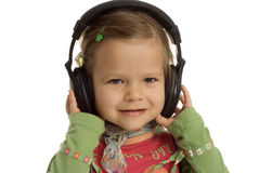 Receiver. Small young girl with headphones on the head Stock Photo