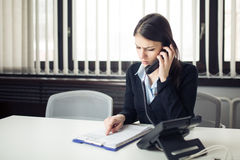 Receiving bad news phone call.Looking confused checking notes and paperwork.Manager solving mistake stock photo