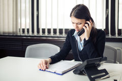 Receiving bad news phone call.Looking confused checking notes and paperwork.Manager solving mistake Royalty Free Stock Photo