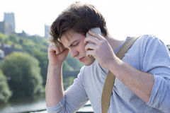 Receiving bad news. A sad male student holds his head in his hands as he uses his mobile phone. He is getting bad news. A cathederal ca be seen in the background Royalty Free Stock Photography