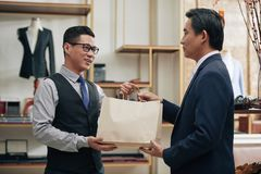 Receiving bespoke suit. Smiling tailor giving customer paper-bag with bespoke suit stock images